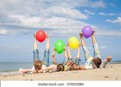 Happy family with balloons  playing on the beach at the day time. Concept of friendly family.