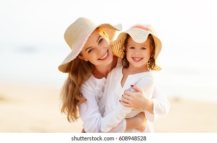 happy family at the beach. motherand child daughter hug at sunset
