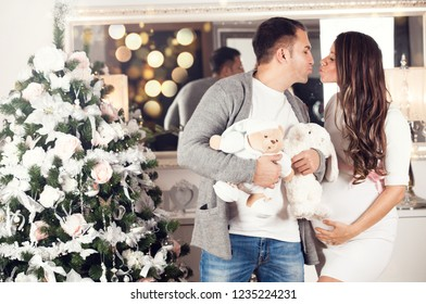 Happy family. Beautiful kissing pregnant couple in love. Merry Christmas and Happy Holidays!