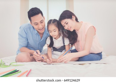 Happy family in the bedroom,Asian father and mother teaching her daughter child to studying at home.Photo series of family, kids and happy people concept.