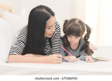 Happy family in the bedroom,Yong mother teaching her daughter child to studying at home.Photo series of family, kids and happy people concept.