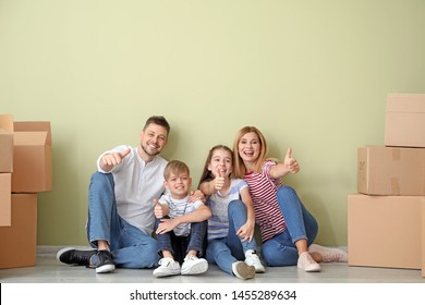 Happy family with belongings showing thumb-up gesture in their new house