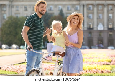 Happy family with bicycle outdoors on summer day
