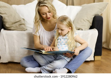 Happy family. Blonde young mother reading a book to her cute daughter while sitting at wooden floor. Motherhood concept