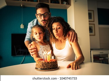 Happy family blowing birthday candles.Celebration concept
