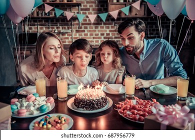 Happy family is blowing candles on cake while sitting at the table in decorated kitchen during birthday celebration