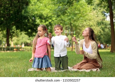 Happy family blowing soap bubbles in park