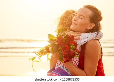 Happy family with bouquet of flowers roses on the beach by the sea at sunset. Young beautiful amazed mother and daughter congratulating happy birthday.Valentine's Day,March 8 International Women's Day