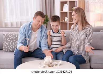 Happy family breaking piggy bank with hammer at home