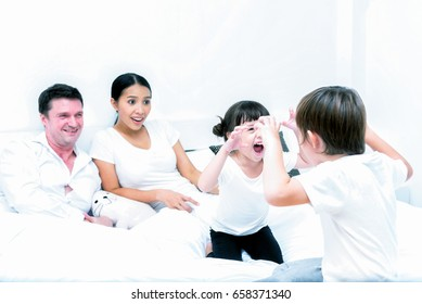 Happy family; Brothers and sisters are playing together on a bed in the bedroom with father and mother in background.
