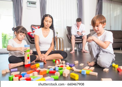 Happy family; Brothers and sisters are playing together with mother and father in the living room at home, happy loving family.