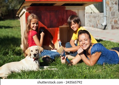 Happy family building a doghouse for their little labrador puppy - painting