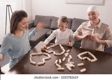happy family building hearts symbols from wooden blocks together, cancer concept