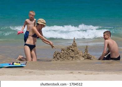 Happy family building sand castles on the beach, Hawaii