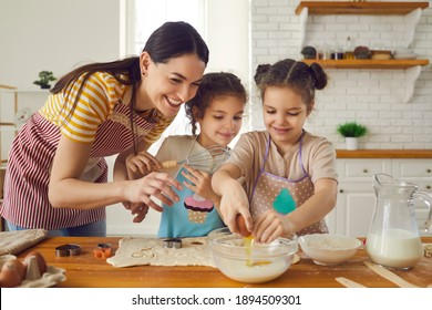 Happy family busy in kitchen. Mother and two helpful little daughters in aprons making cookies on weekend at home. Mom teaches inquisitive children to break egg, prepare dough and use cooking utensils