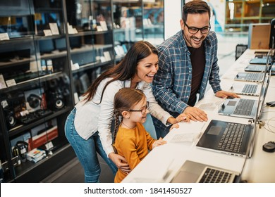 Happy family buying laptop in store.