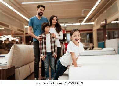Happy family buys new orthopedic mattress in furniture store. Blissful choosing choosing mattresses in store. Orthopedic mattress, for comfortable sleep and healthy posture.