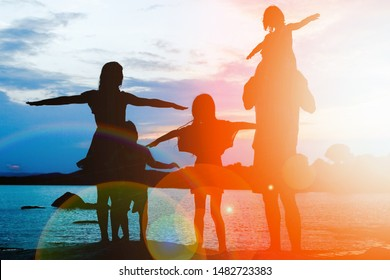 happy family by the sea on nature silhouette background