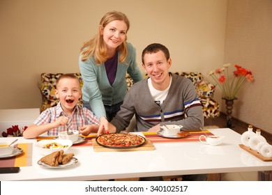 Happy family by the table  with pizza together
