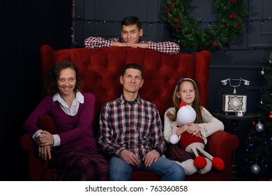 Happy family came together, in anticipation of Christmas - dad, mom with children teenagers are sitting in front of a Christmas tree.
