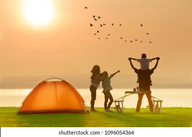 Happy family camping tent near the lake with sunset or sunrise background,happy family concept