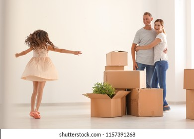Happy family with cardboard boxes after moving into new house indoors