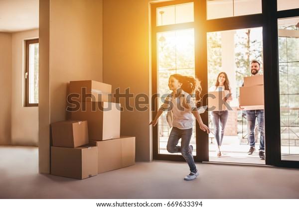 Fröhliche Familie mit Pappschachteln in einem neuen Haus am Tag der Bewegung.