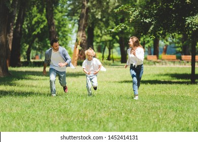happy family in casual clothes running in park during daytime