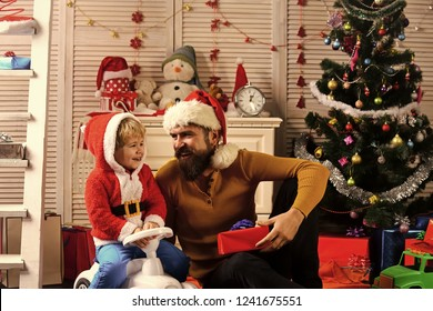 Happy family celebrate new year and Christmas. Father and child on car with new year present box. Winter holiday and boxing day. Father and son in santa hat at Christmas tree. Xmas party celebration. - Shutterstock ID 1241675551