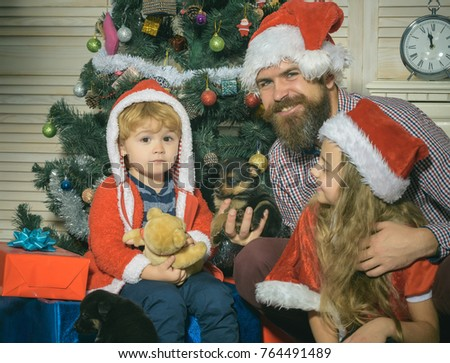 5d729bf8bc132 Happy family celebrate new year and Christmas. Father and child with puppy.  Father and children in santa hat at Christmas tree. Winter holiday and New  year ...