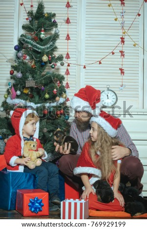 ec1a5d7c2d693 Happy family celebrate new year and Christmas. Father and child with puppy.  Xmas party celebration. Father and children in santa hat at Christmas tree.