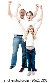 Happy family celebrating with arms up