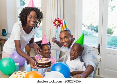 Happy family celebrating a birthday together at table at home in the kitchen