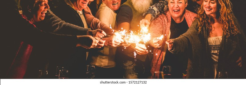 Happy family celebrating christmas holidays and new year with sparkler fireworks - Different age of people having fun together in patio party - Celebration concept - Soft focus on center hands