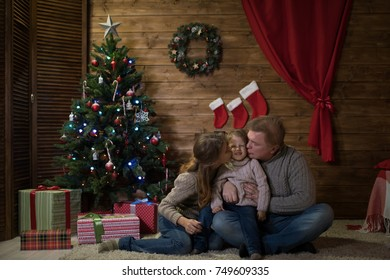 Happy family celebrating Christmas at home, Mom dad and baby sitting on carpet near Christmas tree decorated with Christmas tree, mother and father kiss their beloved child