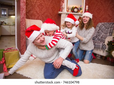 happy family celebrating Christmas near the fireplace under the Christmas tree. Father with children.