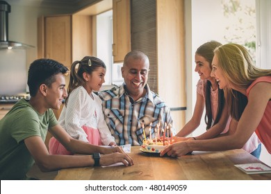 Happy family celebrating the fathers birthday with a cake. They are all crowded round as he blows out the candles.