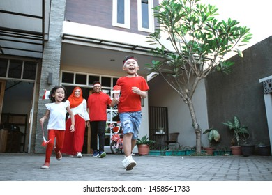 happy family celebrating indonesian independence day together carrying flag and indonesia attributes