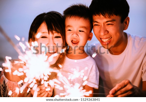 happy family celebrating new year with sparklers