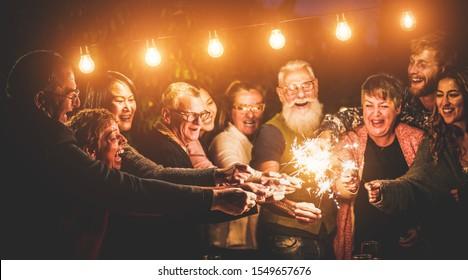 Frohes Familienfeiern mit funkelndem Feuerwerk am Vorabend des neuen Jahres - Verschiedenes Zeitalter der Menschen, die sich in der Patio-Party amüsieren - Feiern, Winter und Feiertage Konzept - Fokus auf links