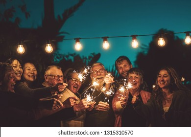 Happy family celebrating with sparkler at night party outdoor - Group of people with different ages and ethnicity having fun together outside - Friendship, eve and celebration concept