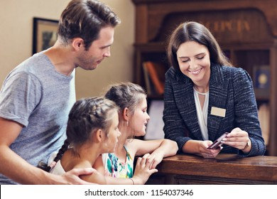 Happy family checking in hotel at reception desk