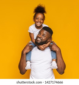 Happy family. Cheerful black man riding his cute little daughter on shoulders, orange studio background