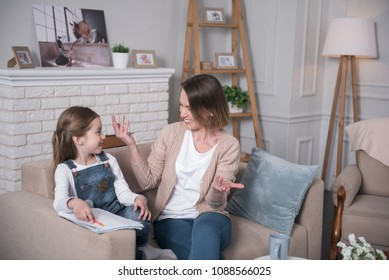 Happy family. Cheerful little girl sitting on the couch with her mother and talking