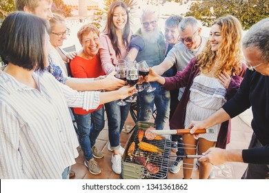 Happy family cheering and toasting with red wine glass at barbecue party - People with different ages having fun drinking and grilling meat at bbq dinner - Friendship, food and weekend activities