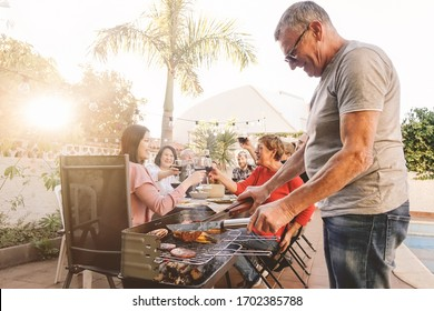 Happy family cheering and toasting with red wine in barbecue party - Chef senior man grilling meat and having fun with parents - Weekend food bbq and reunion young and older people lifestyle concept