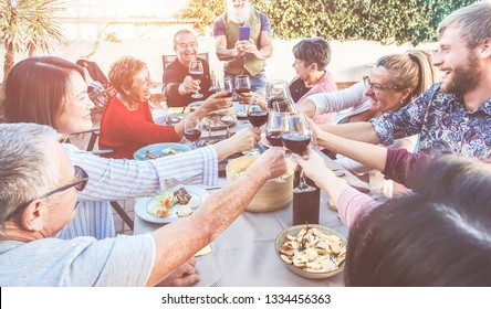 Happy family cheering with wine at barbecue dinner outdoor while hipster father taking photo - Different age of people having fun at sunday meal - Food, summer concept - Focus on close-up glasses
