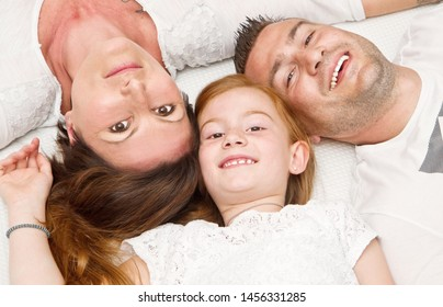 Happy family with child in bed smiling looking at camera