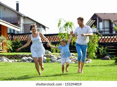 Happy family with a child by the house