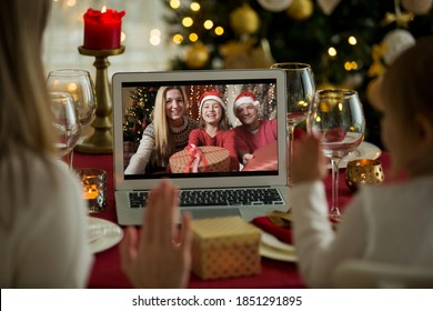 A happy family with a child is celebrating Christmas with their friends on video call using webcam. Family greeting their relatives on Christmas eve online. New normal  virtual event - Shutterstock ID 1851291895